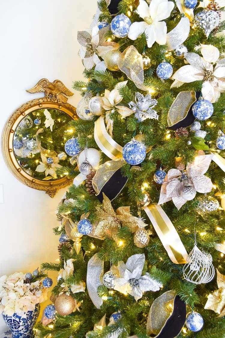 Blue, white, silver and gold ornaments with ribbon and florals on a Chinoiserie