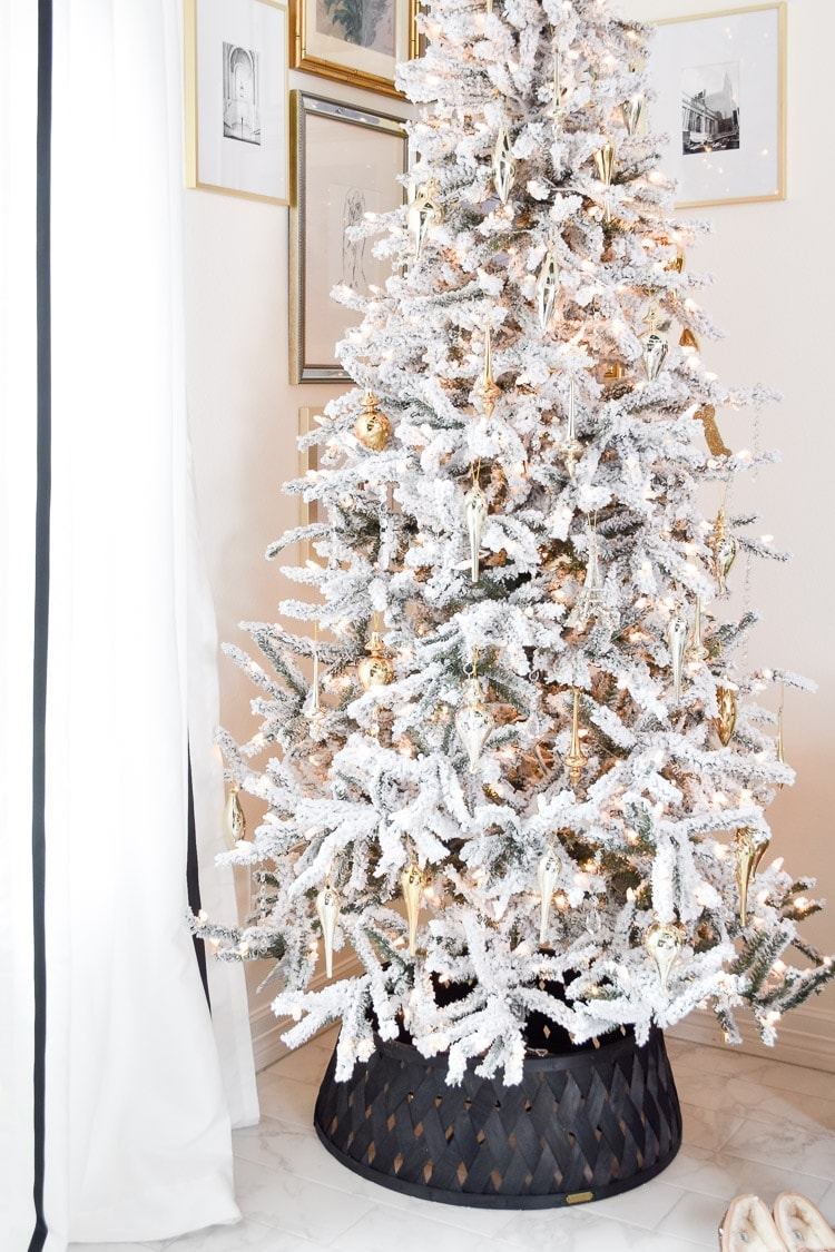 Flocked slim Christmas tree with gold ornaments