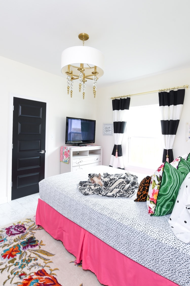 Black and white curtains in a guest bedroom with pink and gold accents