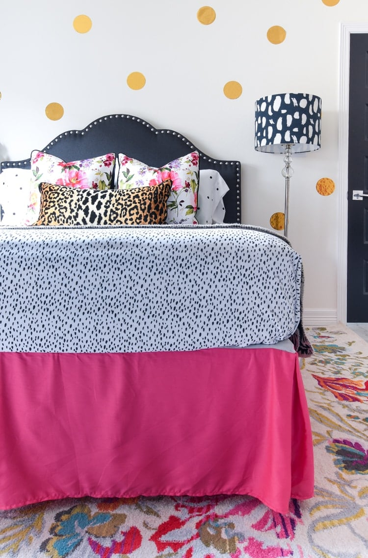 Hot pink bed skirt in a black, white, floral guest room